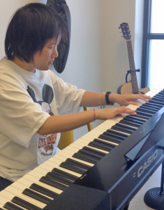 Individual served playing on a Casio keyboard.